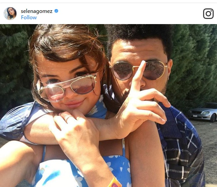 Selena Gomez taking a selfie with boyfriend The Weeknd who has his hands wrapped around her chest, this photo is Gomez's Instagram photo with the highest likes