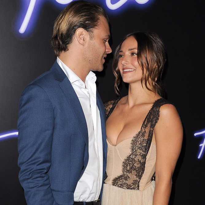 Patrick Flueger and Briana Evigan are cozying up at a public event. Patrick Flueger is wearing blue suit while Briana is wearing a dress with deep cleavage.