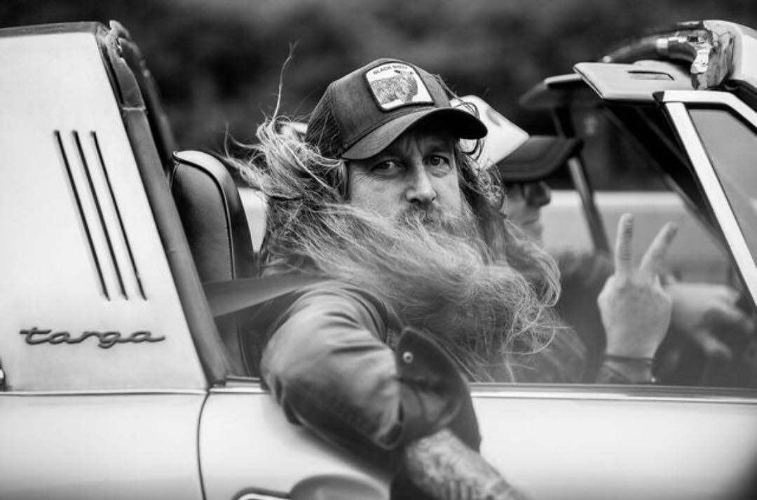 Magnus Walker looking sideways from his Porsche, his beard is being blown along by the wind