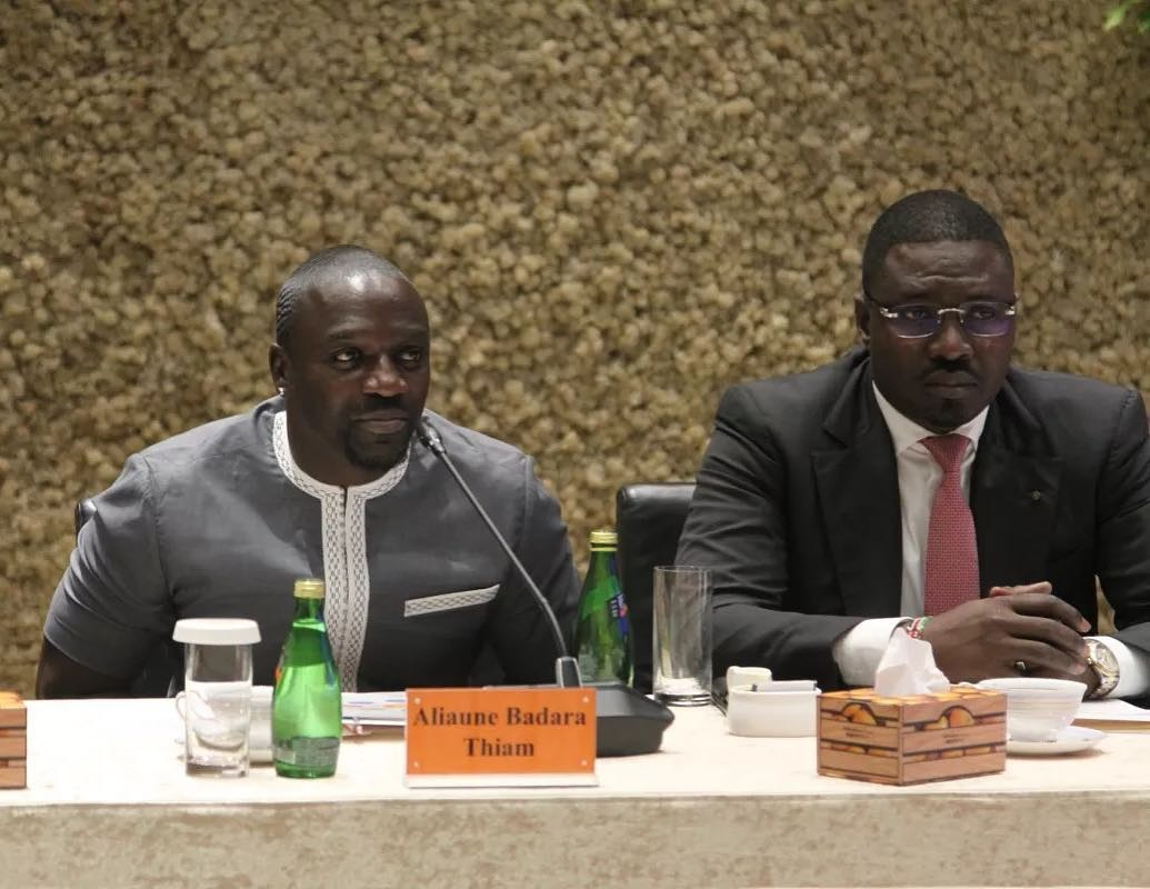 Akon standing in front of the UN logo along with Thione Niang and Samba Sb Bathia Bathily. They are dressed formal.