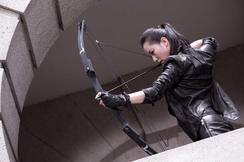 Liu Shishi is pointing an arrow ready to strike a bow, she is wearing black leather outfit which brings up the bold look inher