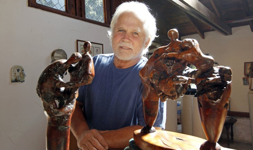 Tony poses alongside his sculptures. He is wearing a blue t-shirt and has grey hair