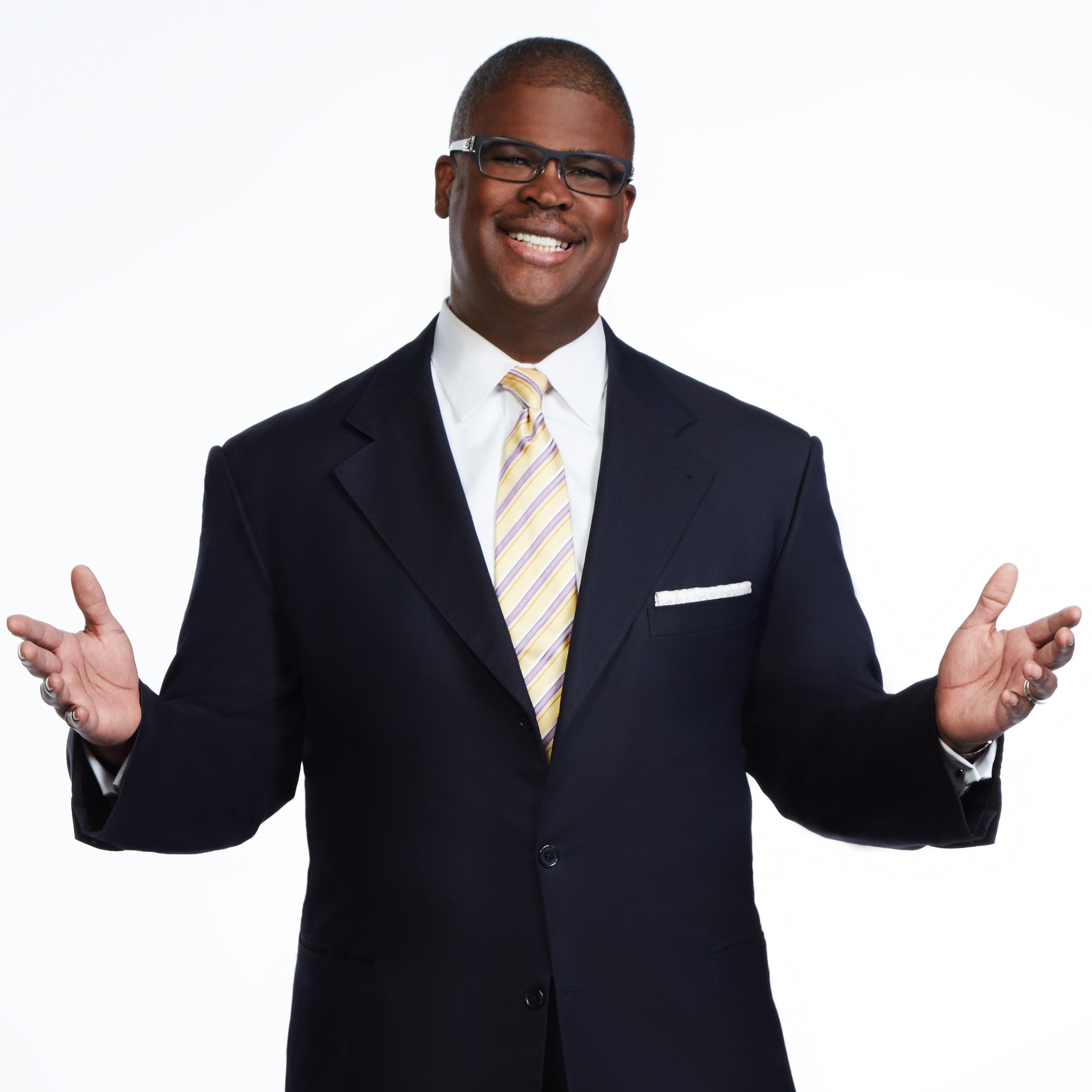 Charles Payne in white shirt and black suit, smiling and spreading his arms