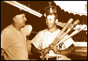 Mickey Mantle smiling, he's holding a baseball bat, there are rows of bleachers in the background
