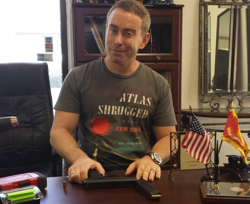 Craig Gottlieb sitting on desk with his hands on a gun