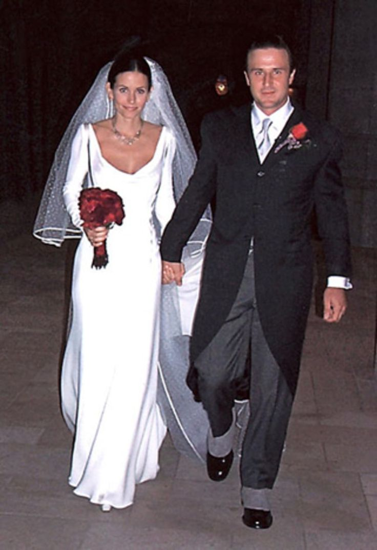 Courteney Cox in a white dress with David Arquette who is in a suit. They are holding hands while Cox holds a bouquet in her other hand.