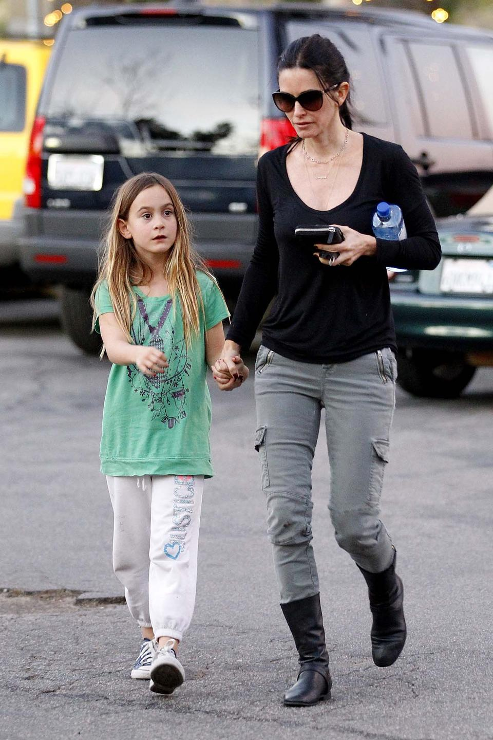 Courtney Cox holding her daughter Coco Arquette's hand while they walk