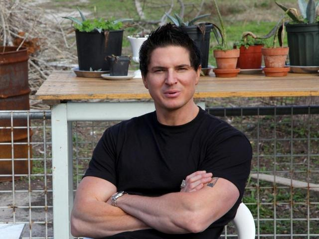 Zak Bagans is smiling in the camera