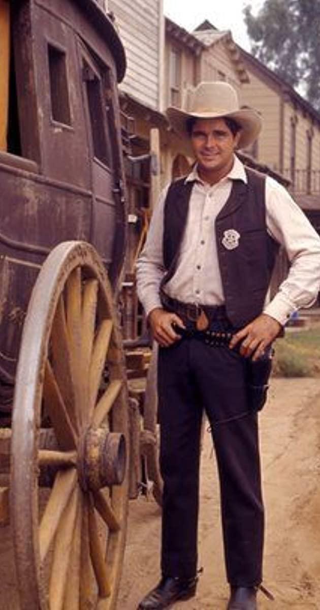 Buck Taylor standing alongside a wagon on the set of Gunsmoke. Buck Taylor played the role of Newly O'Brien in Gunsomke.