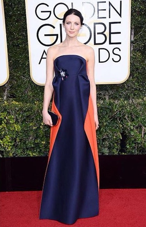 Caitriona is looking flawless in her attire. The dress is simple and is looking magnificent on her sculpted body. She poses for a photo with her beautiful blue and orange dress. She is carrying a black clutch in her right hand which looked perfect with her dress.