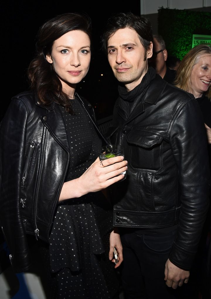 Caitriona Balfe and her fiance, Tony McGill are posing for the camera. Both are wearing black attire with Caitriona holding a drink in her hand.