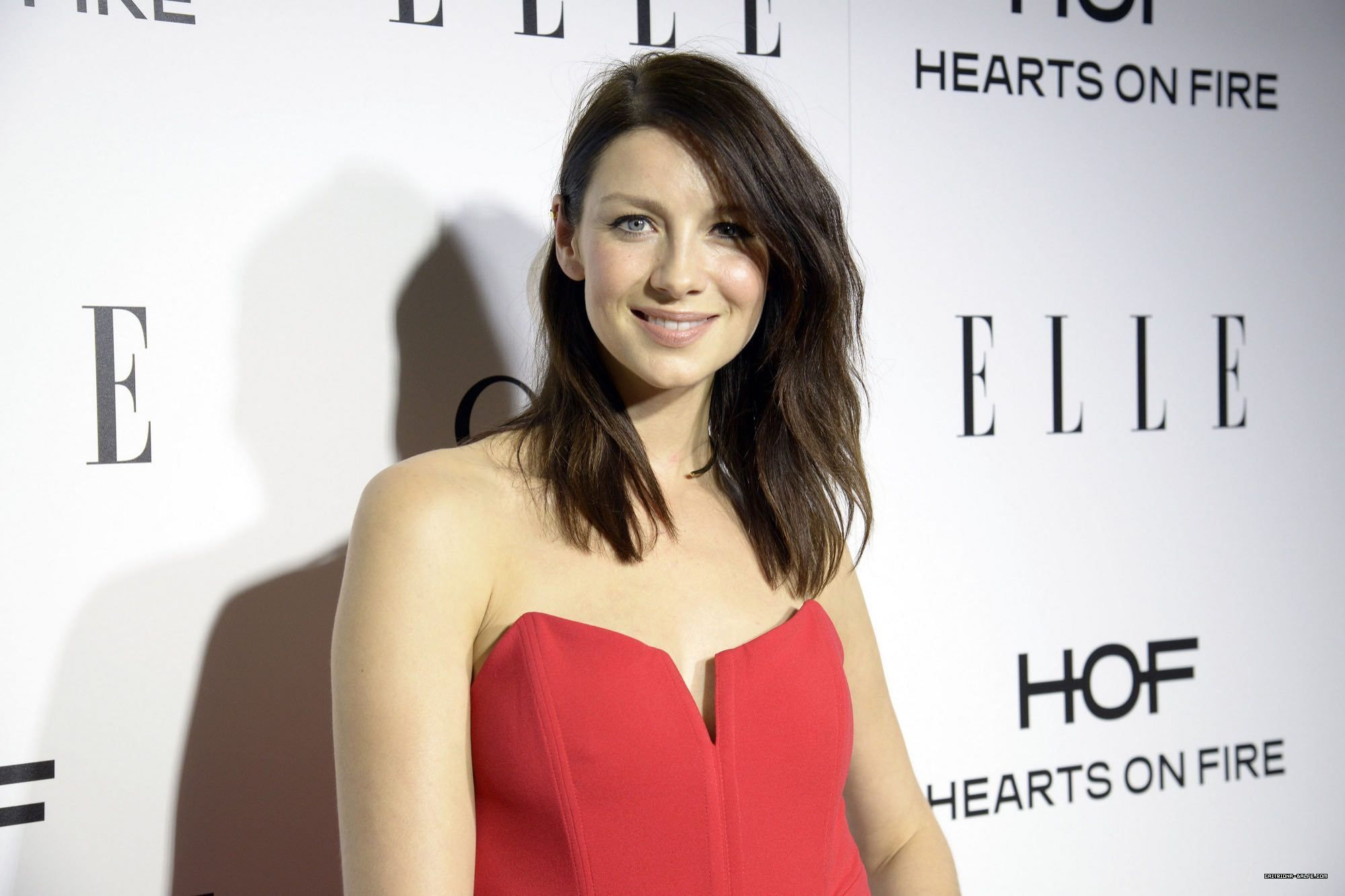 caitriona balfe at a ELLE show  wearing a red dress