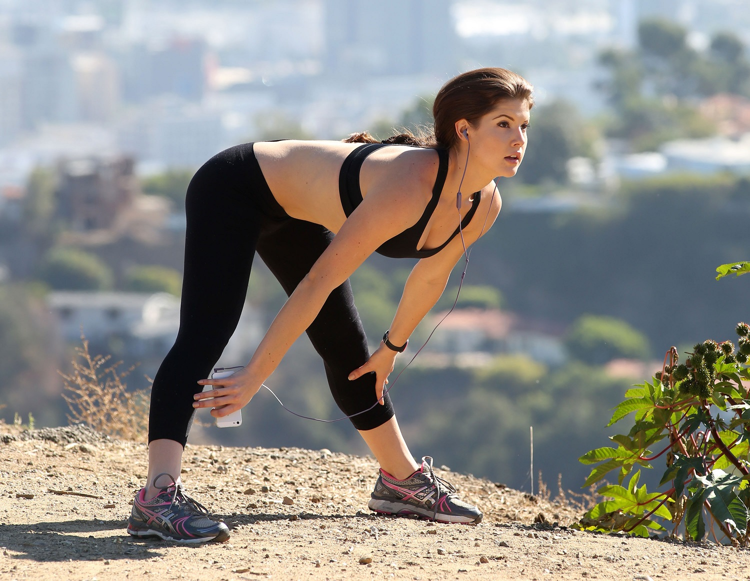 Amanda Cerny is working out in an open space. She is wearing a black sports-bra and a black yoga pant. She is holding a mobile phone in her right hand and has earphones plugged into her ears.