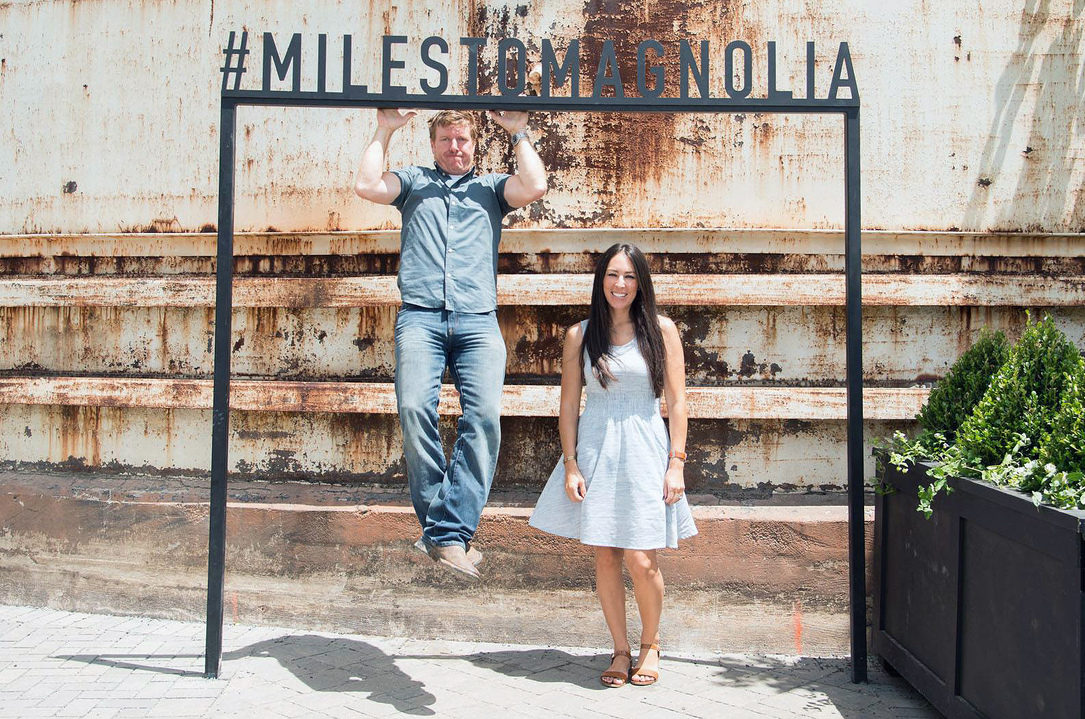 Chip and Joanna posing for a picture. Chip is doing pull ups on a stand that days #MILESTOMANGOLIA and Joanna is standing smiling white dress