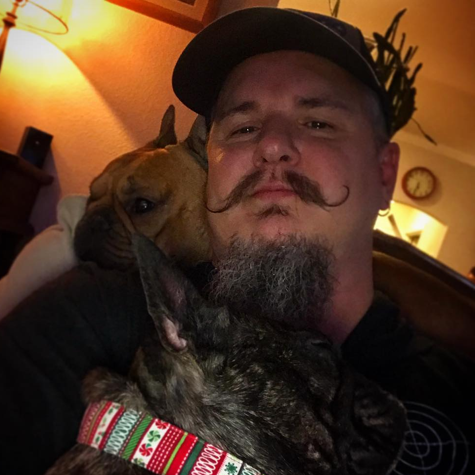 Chris Loesch is lying with his two French bull dogs, Rocco and Louie.