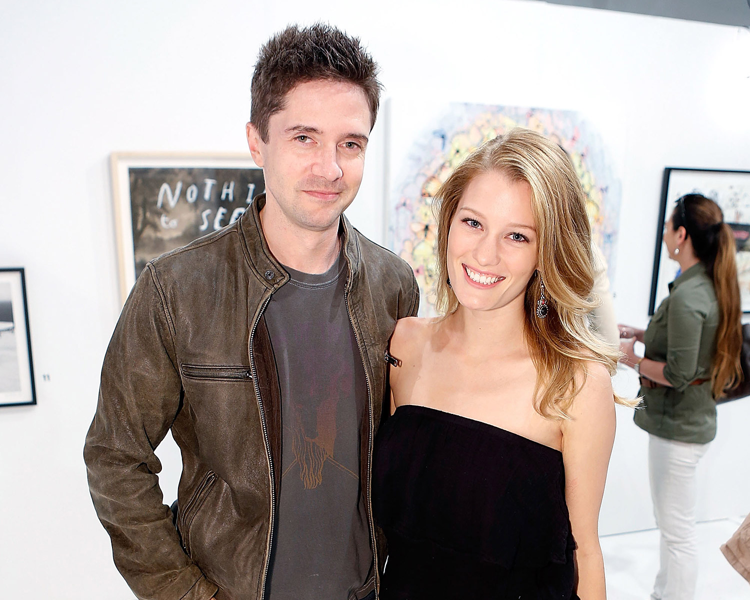 Topher Grace and his wife Ashley Hinshaw are standing close to each other as they pose for the photograph. Ashley is wearing a strapless black dress and Topher is wearing leather jacket.