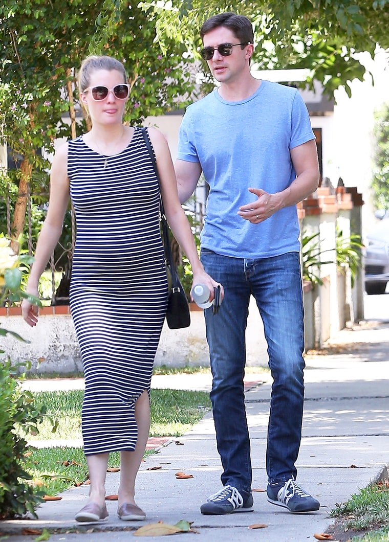 Ashley Hinshaw and Topher Grace walking. Ashley is carrying a side bag and is holding a water bottle and phone on one hand. Topher Grace is walking behind him. Both of them are wearing sunglasses.