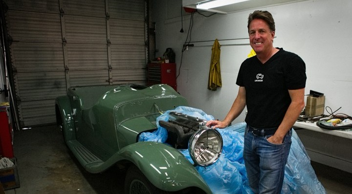Dennis Collin is looking in front of the camera posing standing in front of his car. He is smiling and he is wearing a black T-shirt bearing small car logo, and a jeans.