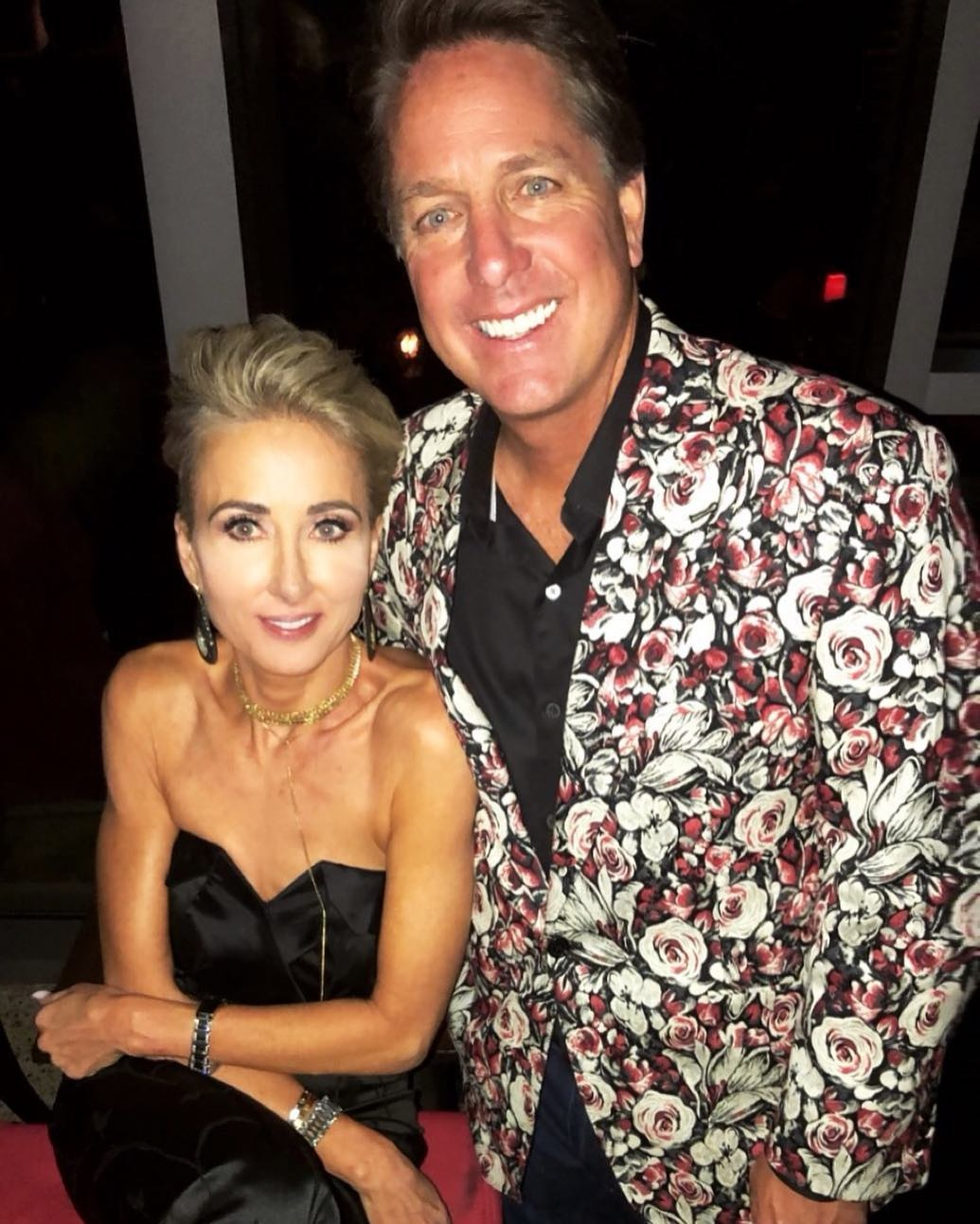Dennis Collin is posing for the camera with a broad smile alongside his wife, Kimberly Collins. Dennis is wearing floral print coat and his wife is wearing strapless black dress.