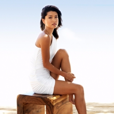 Actress Grace Park posing for the camera while sitting on a wooden bench. She is wearing a hot white dress.