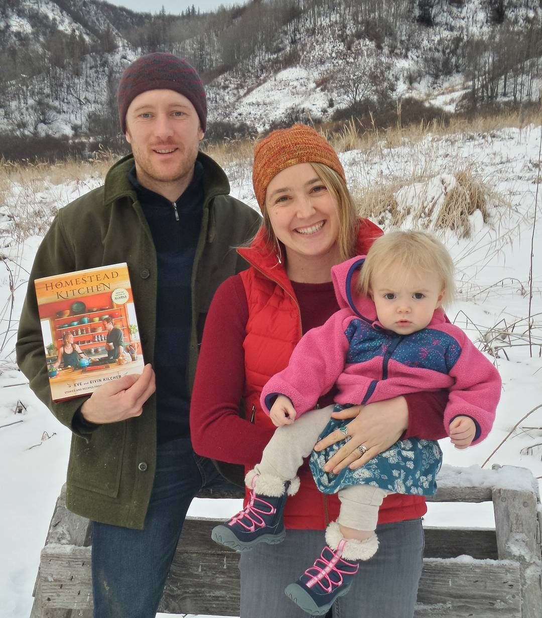 The Kilchers posing for a picture. Eivin is holding a book and Eve is carrying their child wearing winter clothes