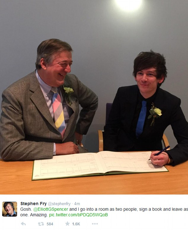 Stephen Fry is smiling facing Elliott Spencer as he is writing something holding a pen in his left hand.