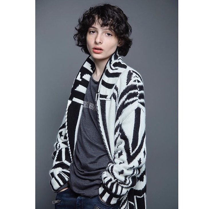 Finn Wolfhard is wearing a black and white outer