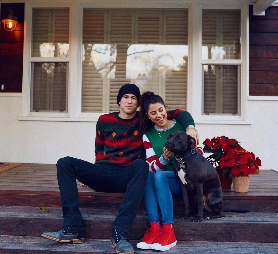 Daniella Monet and her boyfriend Andrew Gardner, along with a dog, are sitting on the stairs outside their house.