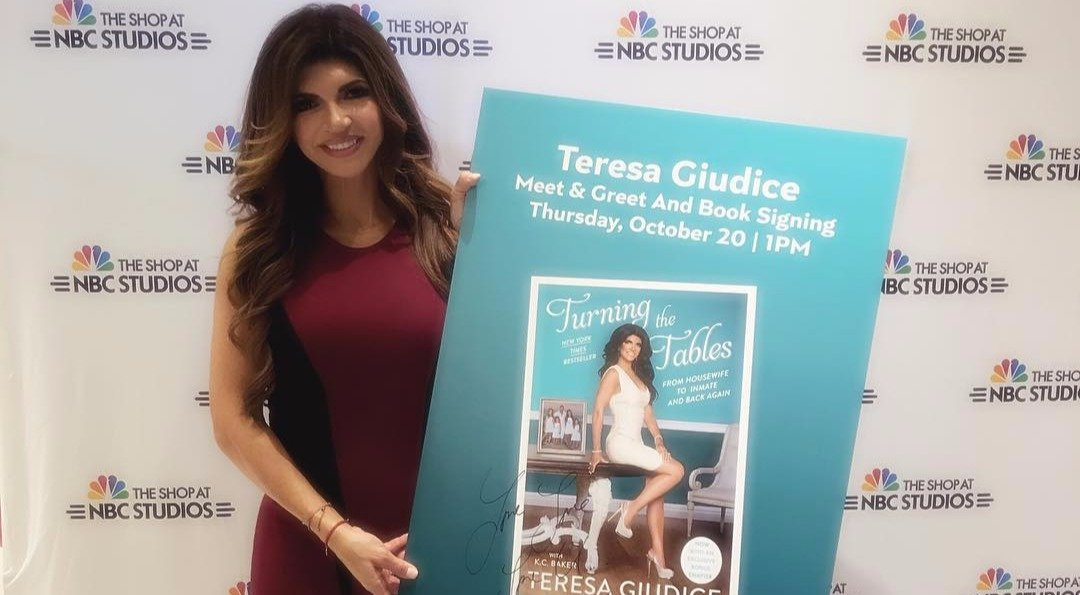 Teresa Guidice leaning her hand on a wall, her other hand's on her hip, one of her legs is bent at the knee