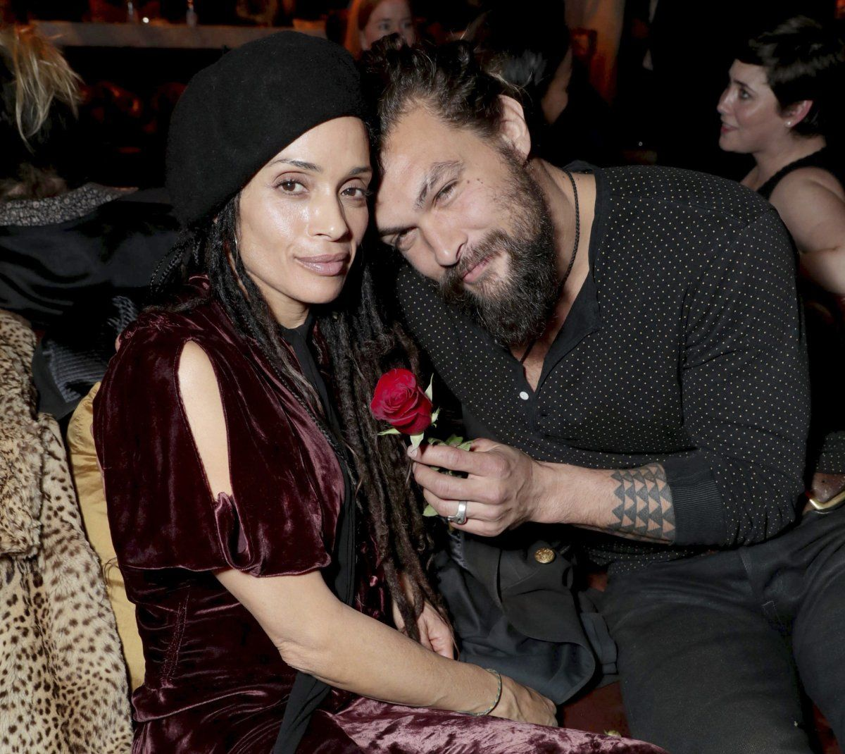 Jason and Lisa smiling for a picture. Jason is holding a red rose. Both are wearing black attire