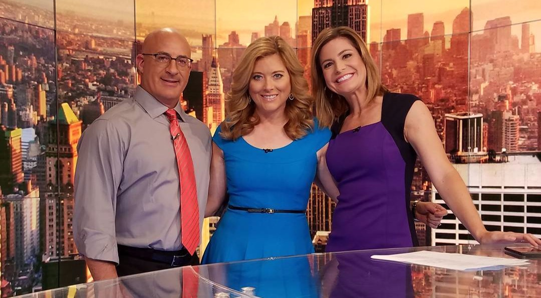 Kelly Cass on The Weather Channel studio with meteorologists Jen Carfagno and Jim Cantore. They are celebrating the 34th anniversary of The Weather Channel.