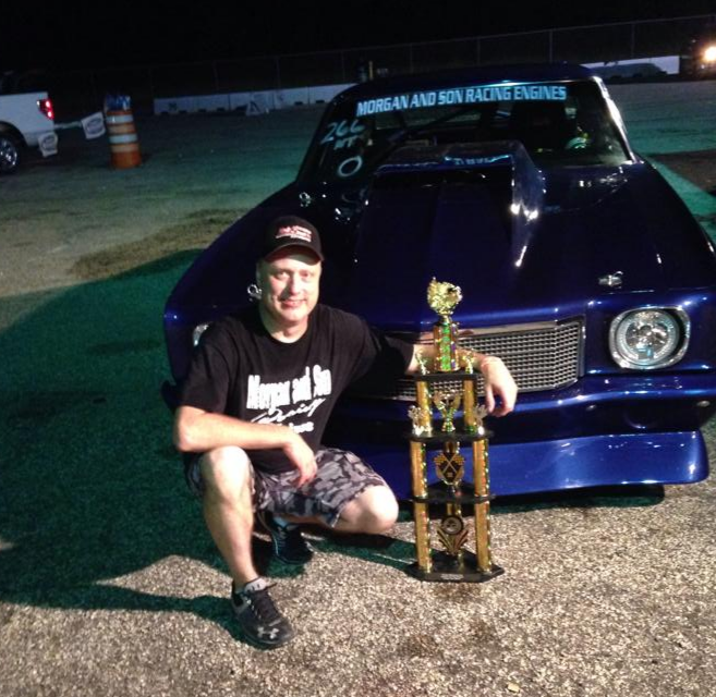 "James ""Doc"" Love sits in front of his car, The Street Beast, holding a trophy."