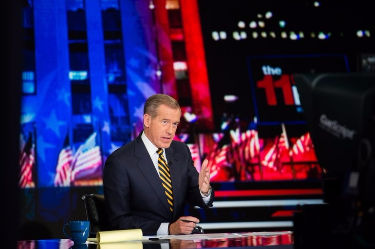Brian William in the sets of NBC's 11th Hour. He is using his hands gesture. He is dressed all formal and the set he is in holds American flags flapping.