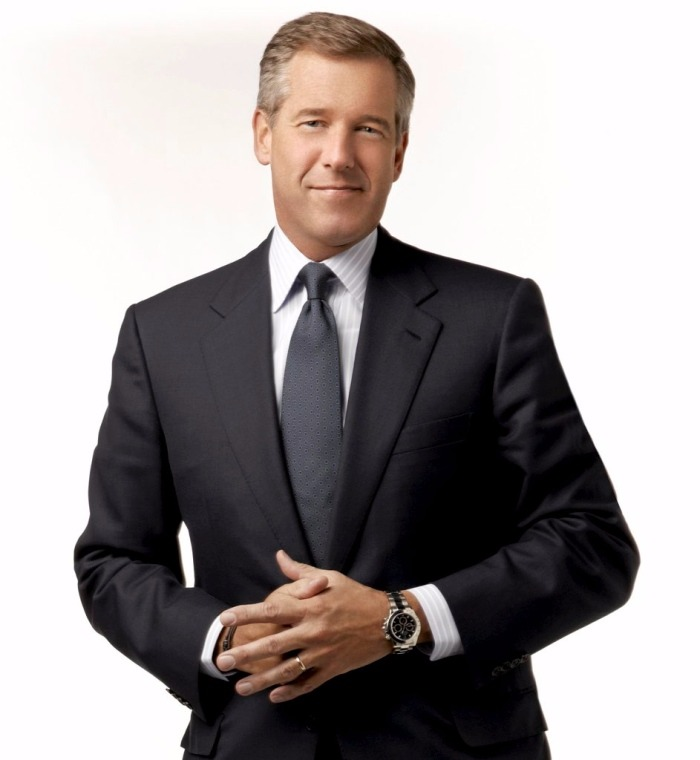 Brian Williams looking smart and bold in his formal look. He is wearing a black suit, tie and a white shirt. He is smiling.