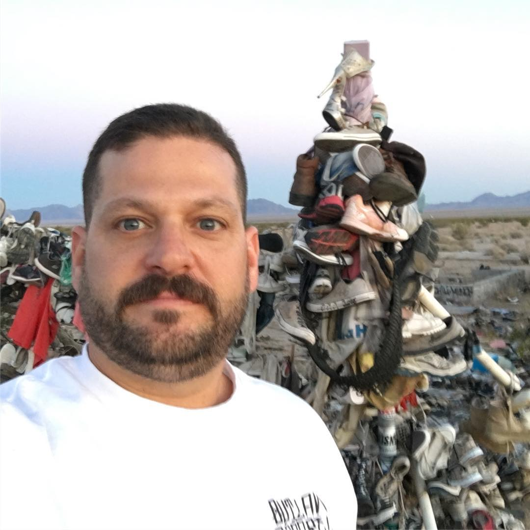 Jarrod Schulz is standing in front of piles of shoes