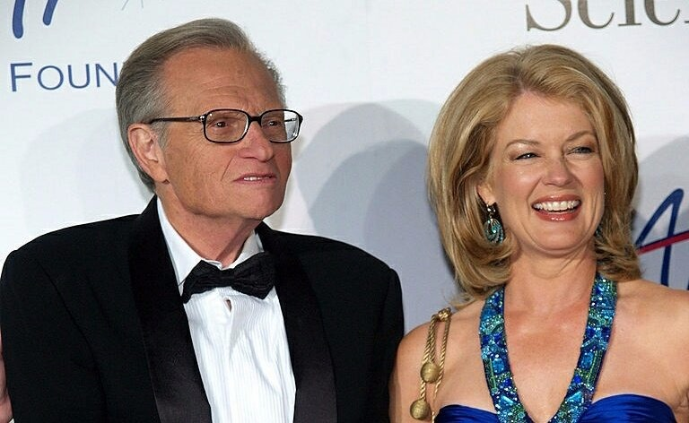 Mary Hart looking glamorous in her sleeveless naive colored dress. She is standing next to Larry King.