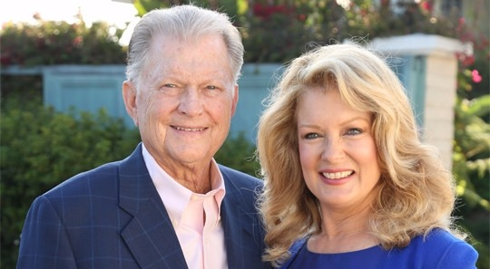 Mary Hart and her husband Burt looking perfect together. Burt is wearing a dark blue suit and pink shirt and Mary is wearing a dark blue dress, they are both smiling.