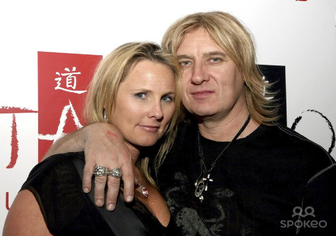 Joe Elliott is draping his arm around the shoulder of his current wife Kristine.The blonde couple is smiling to the camera.