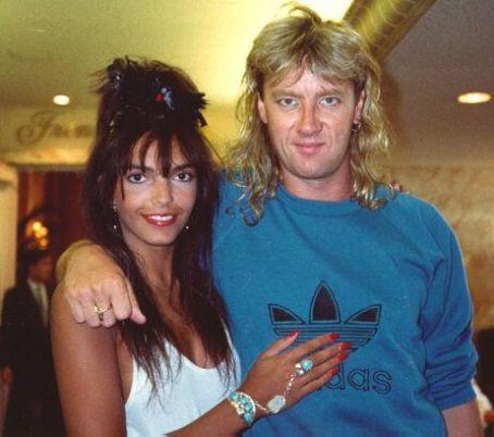 Joe Elliott is draping his arm around the shoulder of Karla Ramdhani, his former wife. Karla is half-embracing Elliott.