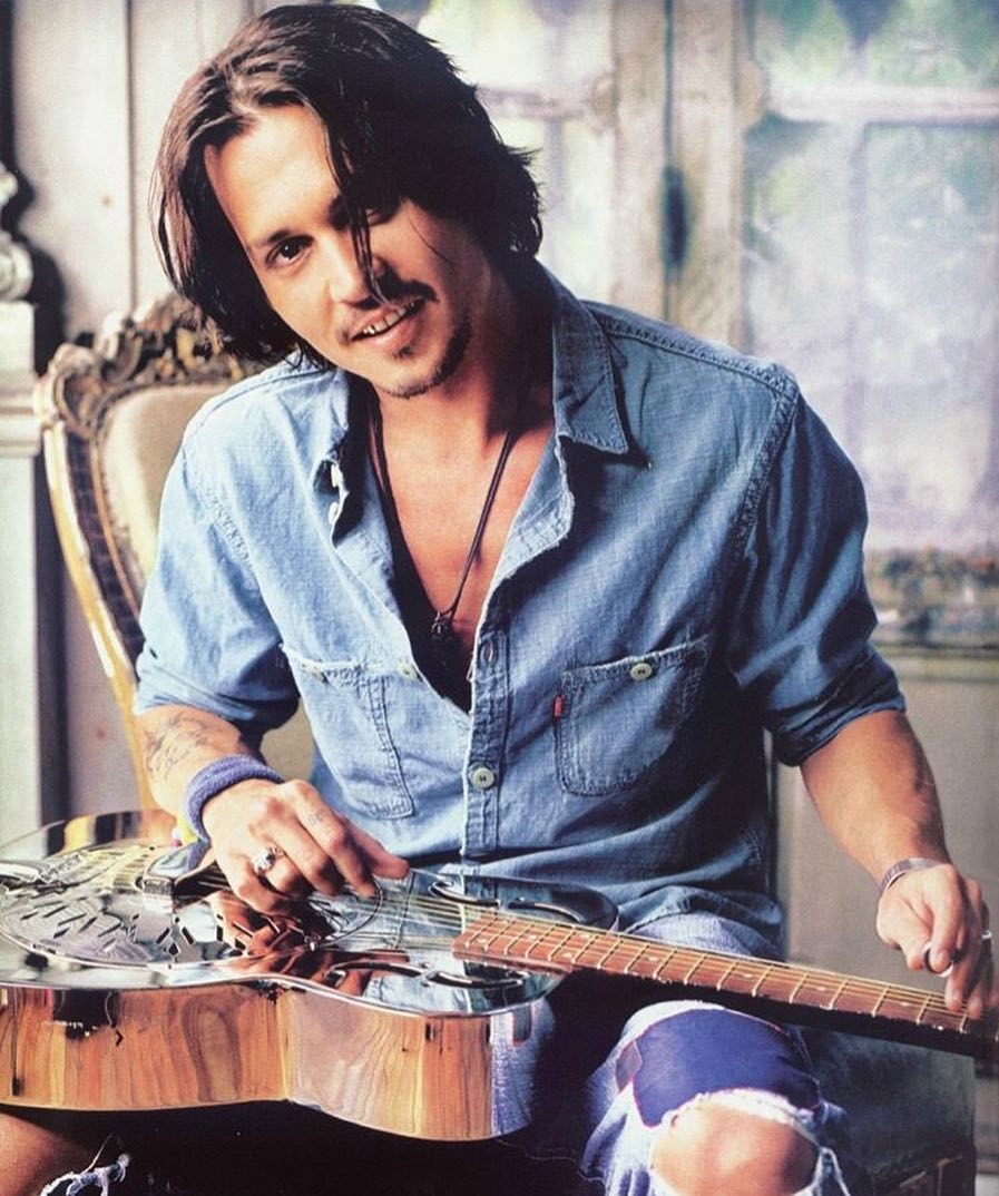Johnny Depp has a guitar in his hand