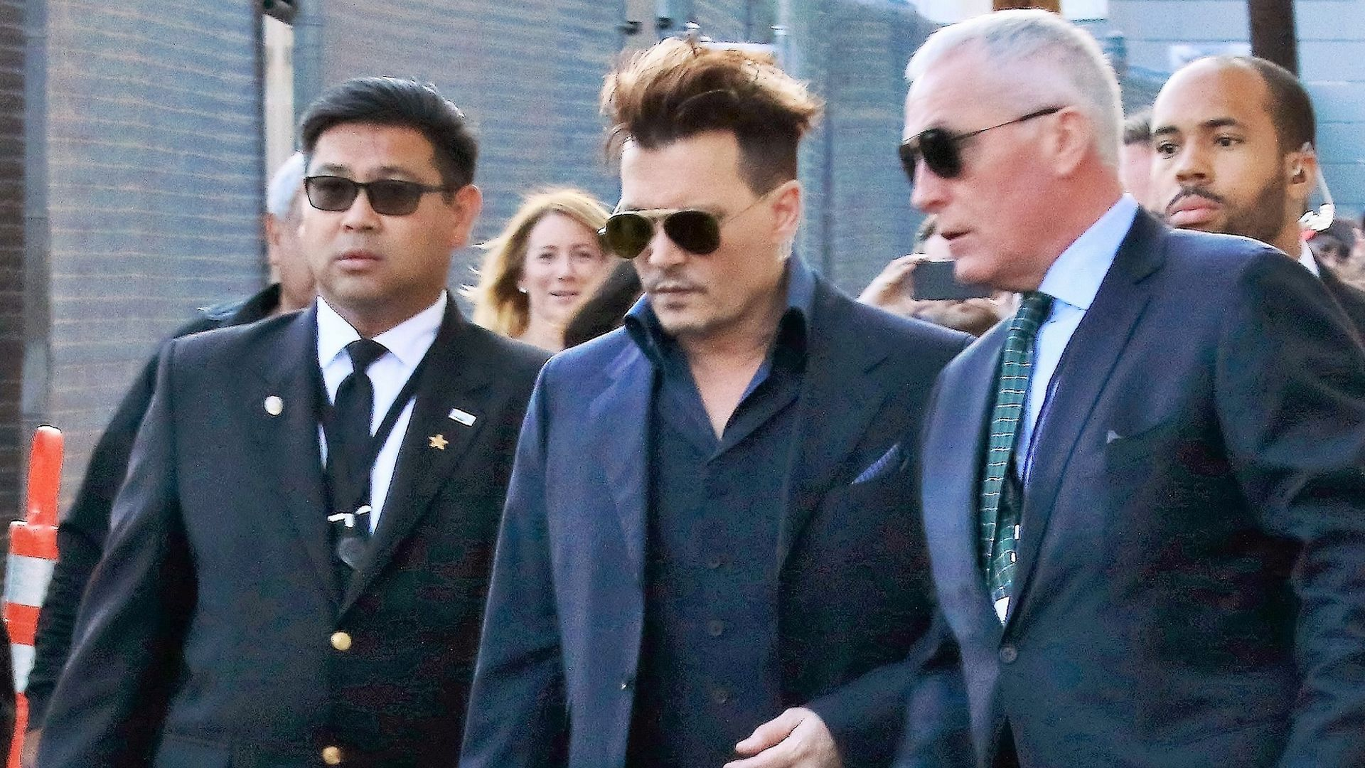 Johnny Depp walking with his personal security guards