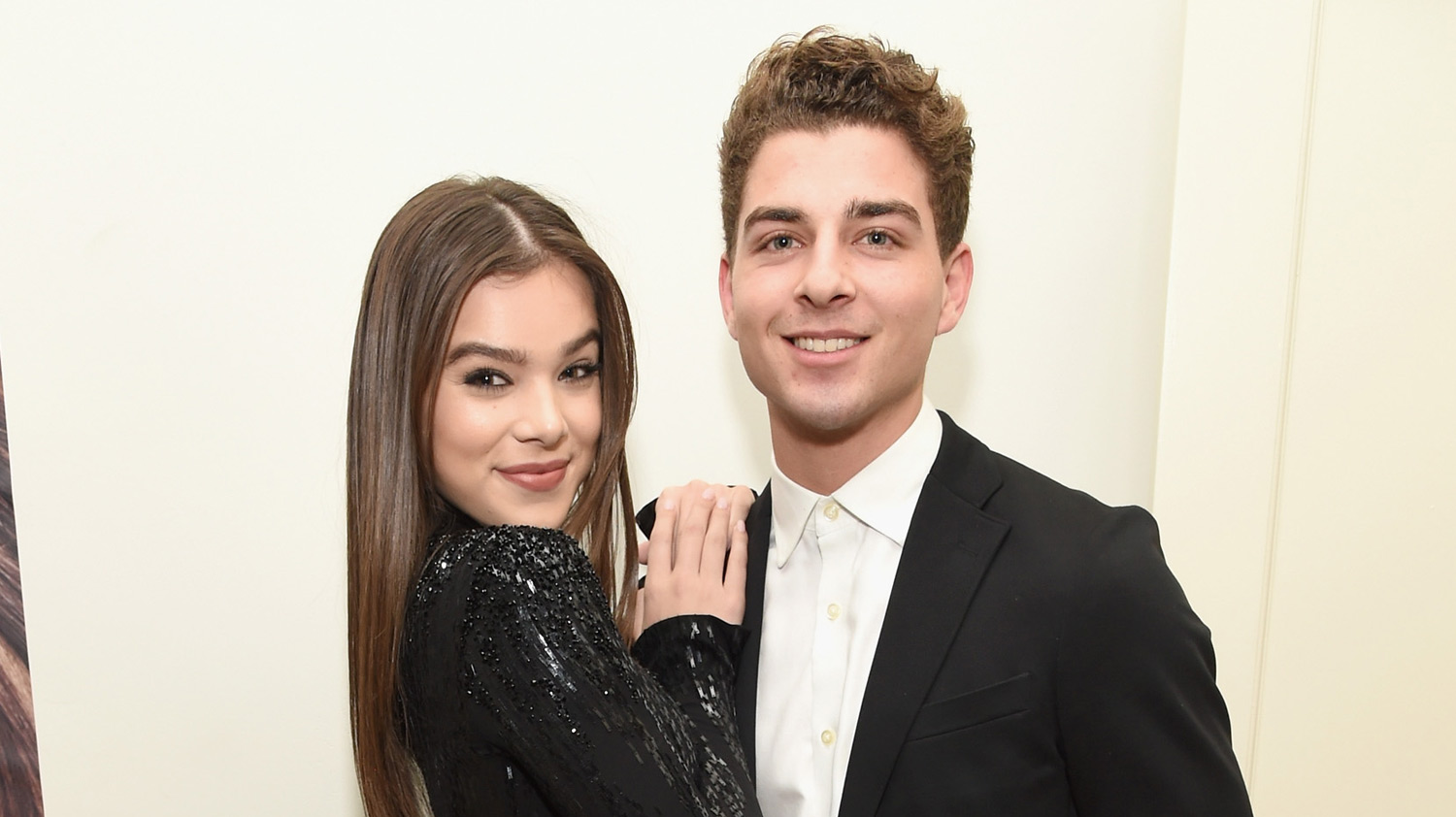 Hailee Steinfeld puts both her hands in Cameron Smoller's shoulder as they smile for a picture