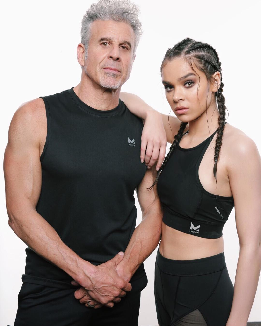 Hailee is resting her hand on her fathers shoulders while they look to the camera. Peter Steinfeld has his hands in the front and folded.