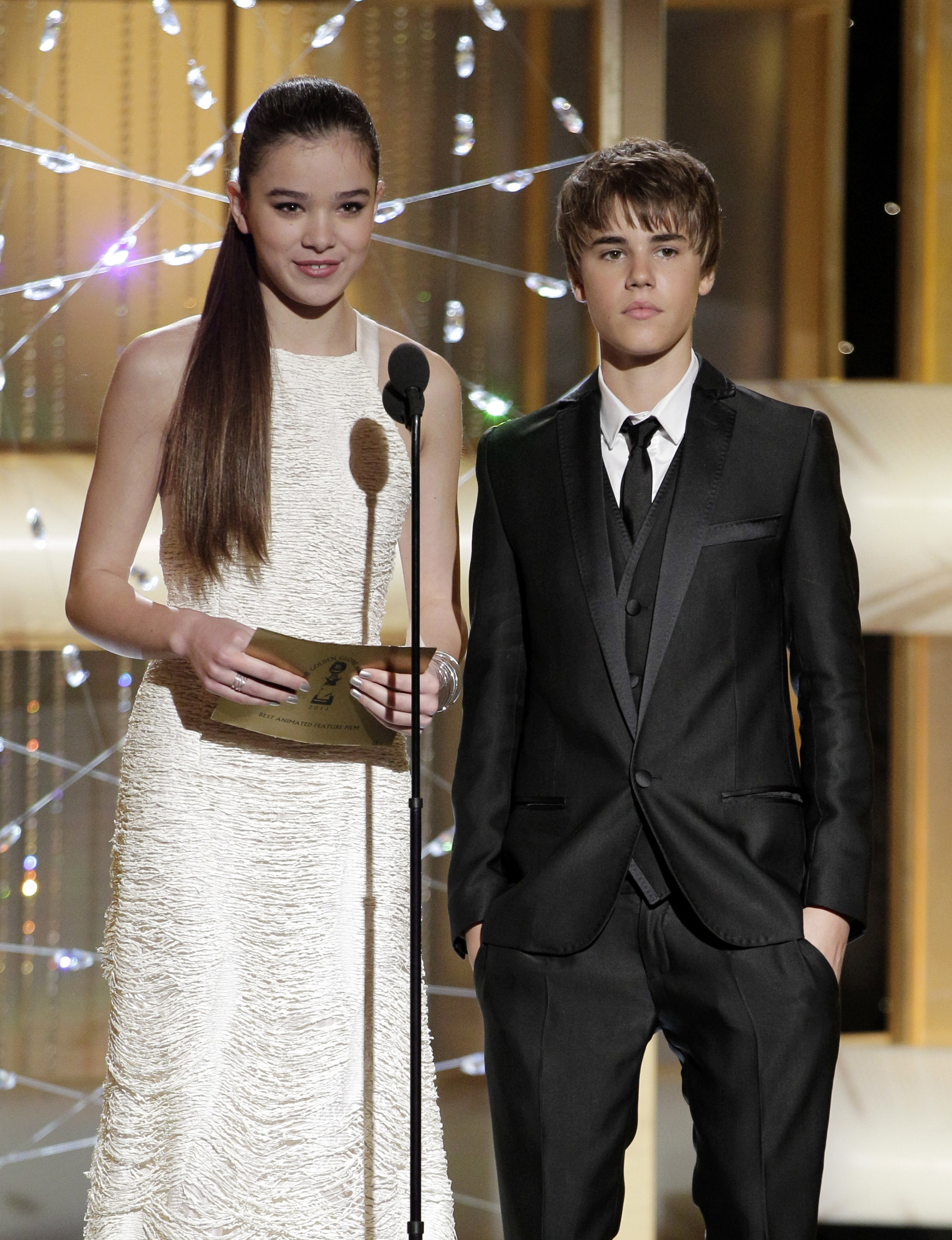 Hailee Steinfeld and Justin Beiber standing close to each other as they look towards the audience. Hailee is holding a sheet of paper in her hands