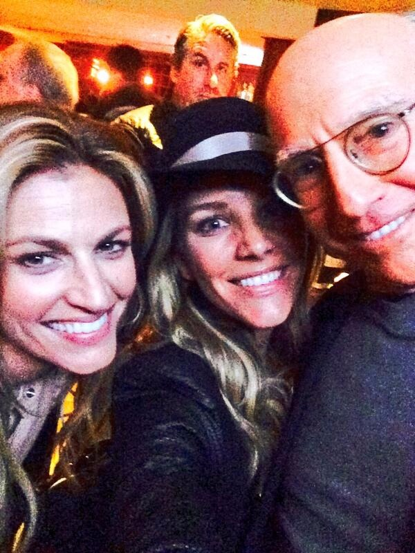 Charissa Thompson is wearing a black hat, she has her long hair left open, she is taking a selfie with Larry David and  Erin Andrews