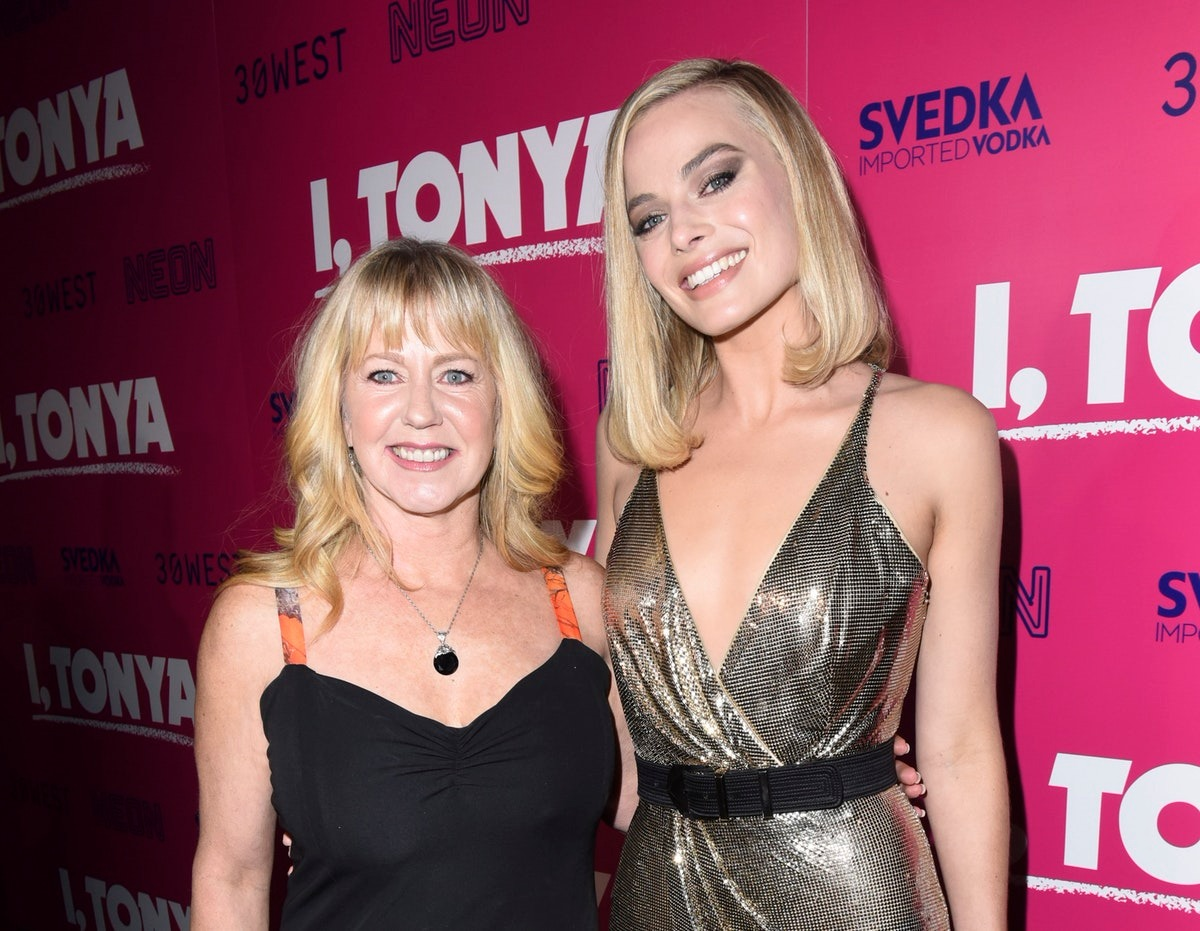 Tonya Harding is standing alongside Margot Robbie in an event. She looks dashing in their black fancy dress. She and Margot are both smiling as they pose for the picture.