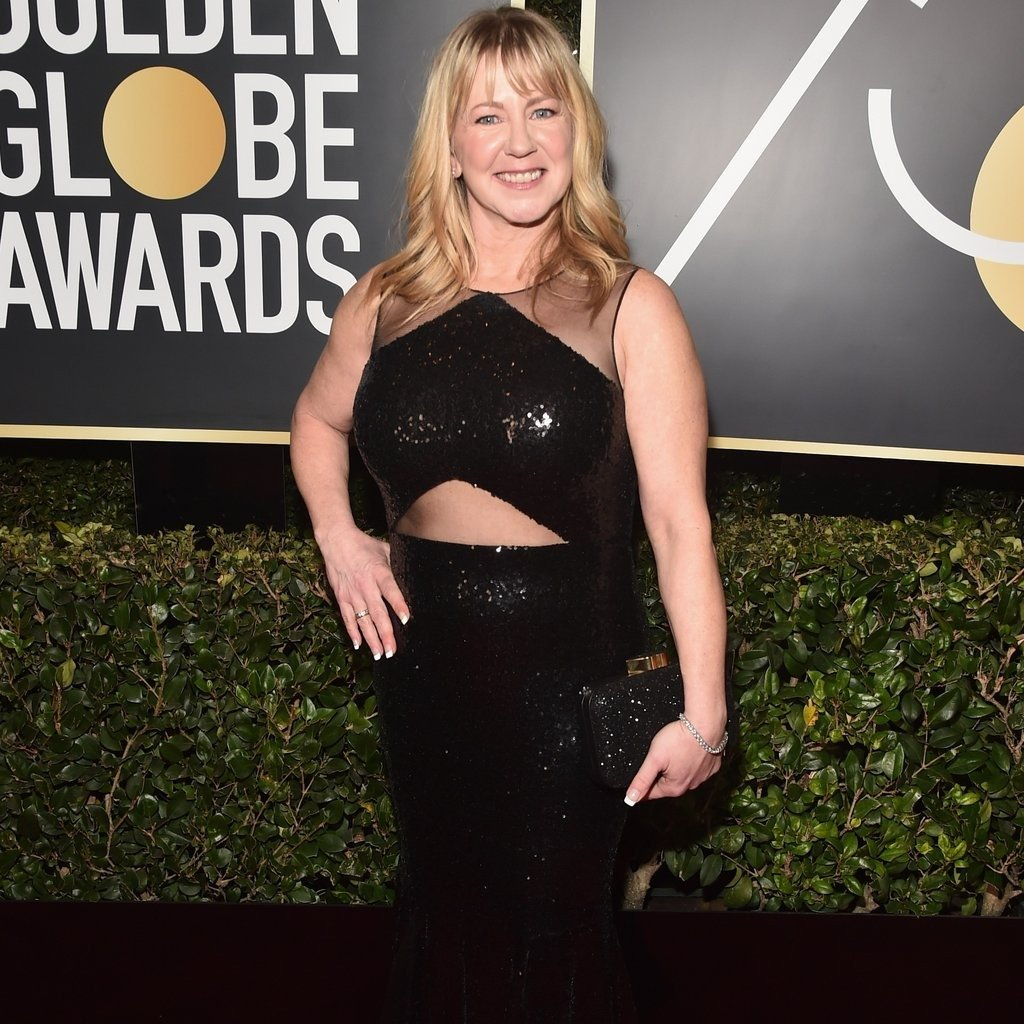 Tonya Harding poses on the red carpet of Golden Globe Awards. Her shiny black dress compliments with her personality in the perfect way. She puts her right hand on her waist and with other, she holds a matching shiny purse.
