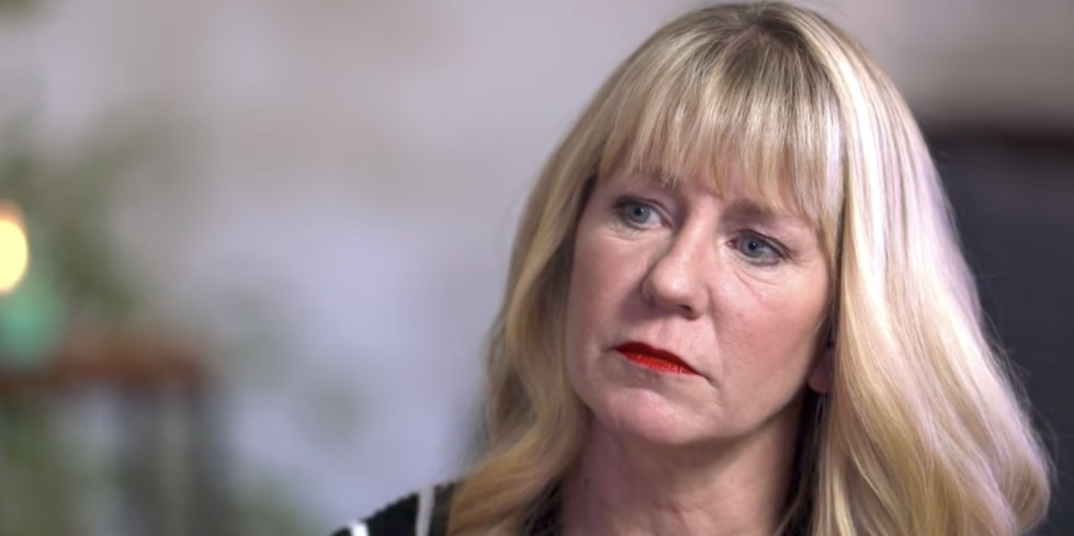 Tonya Harding sits on the studio appearing for an interview. She is looking away from the camera and giving a thoughtful look when the picture is taken. She looks stunning with her blonde hair.