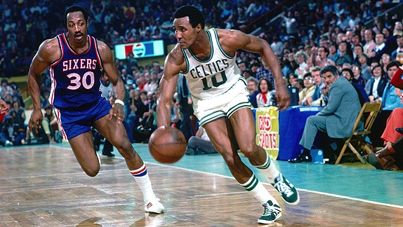 Jo Jo White is dribbling ball while is opponent is coming for the ball. He is wearing white colored Celtics' jersey.