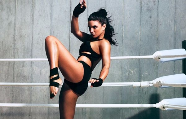 Gina Carano helds her one leg up and bends it from the knee showing some of her martial art skills.